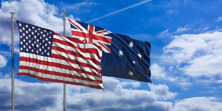 Australia and USA Flags with a Blue Sky Background