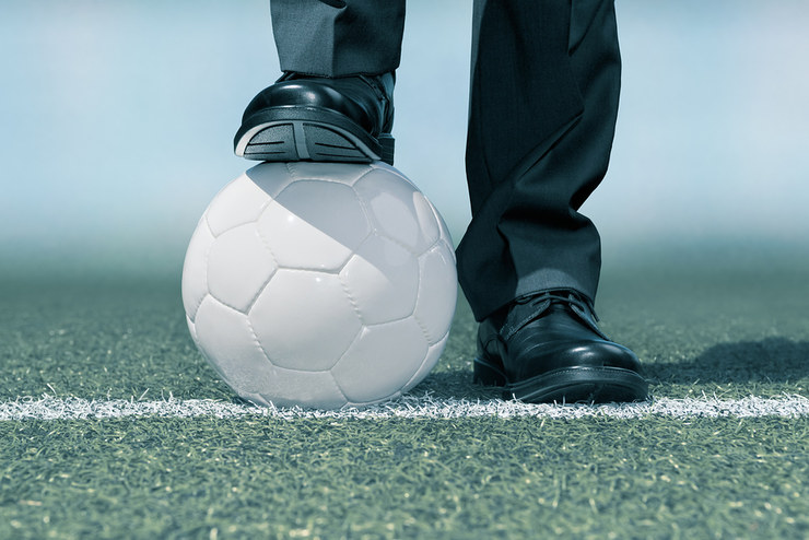 Football Manager Standing on Ball